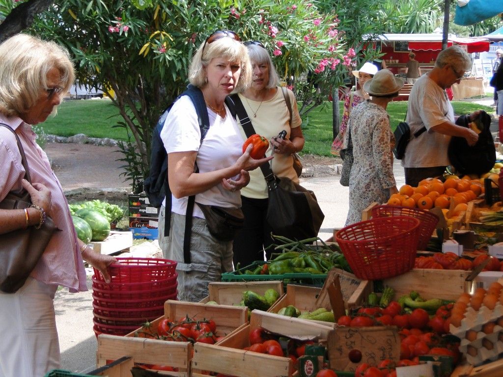 Jill and Dawn collaborating on selecting the finest local produce from the open-air market